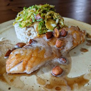 Recipe image of Brown Buttered Rockfish and Toasted Almonds. Served on a pottery style plate with rice topped with slaw.