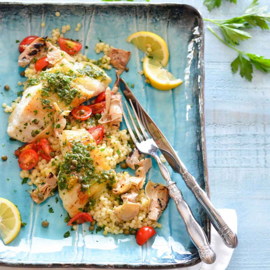 Recipe image for Lingcod with Spanish Salsa Verde served on a blue plate on light blue wooden table.