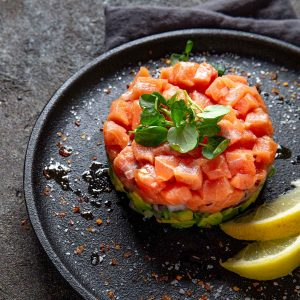 Salmon Poke with Avocado displayed in a circle on a slate colored plate.