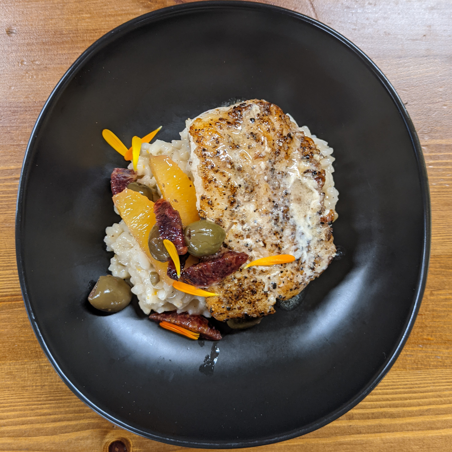 Spice crusted Lingcod on a bed of risotto with olives, and orange slices.