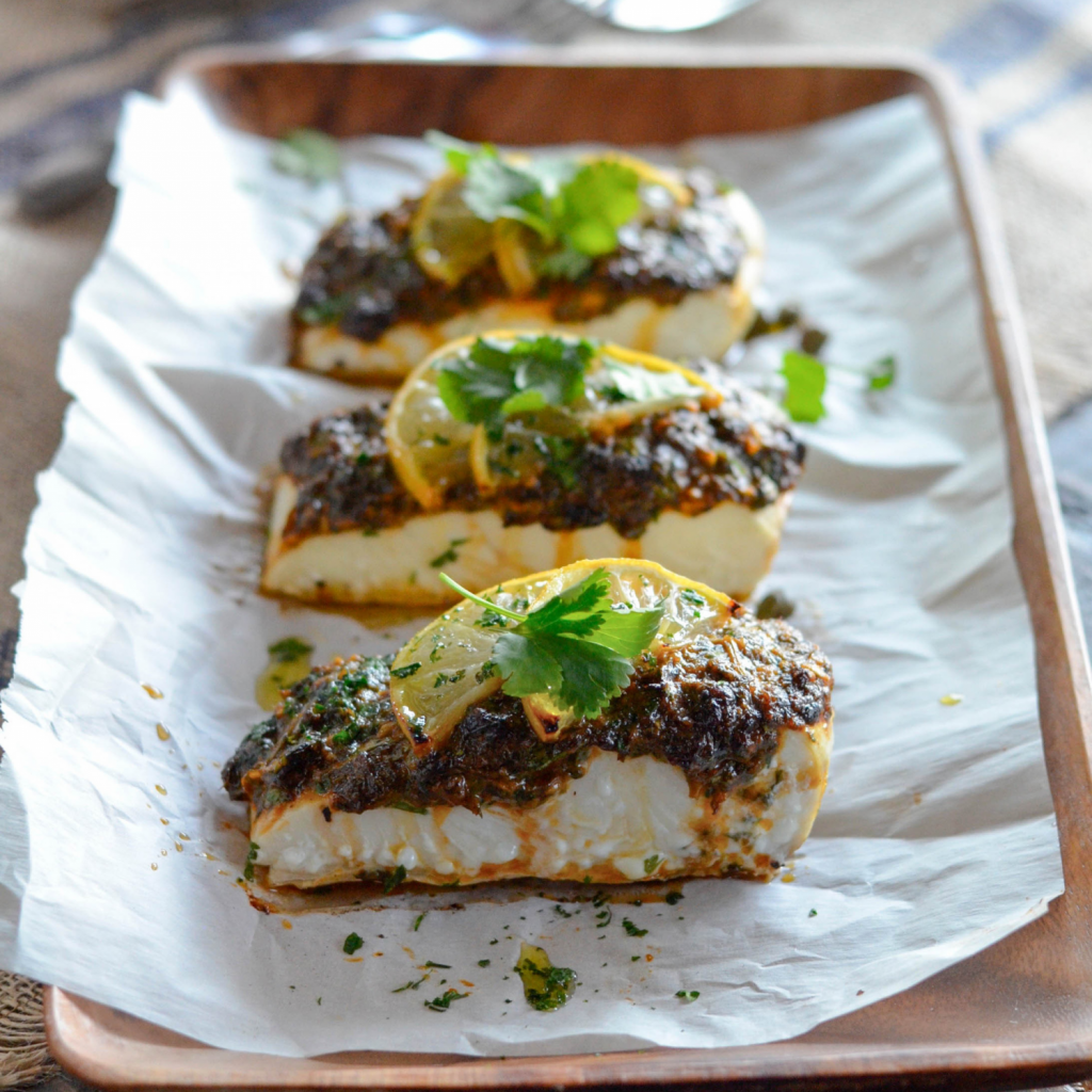 Beautiful plated shot of herb-crusted fish with lemons garnishing each fillet..